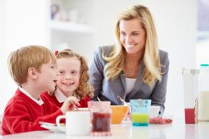White British Mother And Children Having Breakfast In Kitchen Together